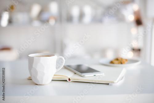 Fotomural Modern white office, designer handmade cup of coffee, smartphone