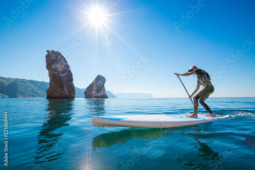 Young Man Having Fun Stand Up Paddling in the sea. SUP. Guy Training in the morning on Paddle Board near the rocks.