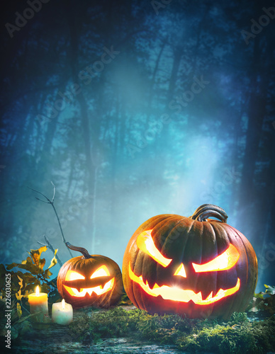 Jack o' lanterns glowing at moonlight in front of spooky forest