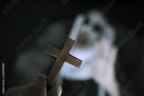 Canvas Print frightening evil nun screaming in front of a cross