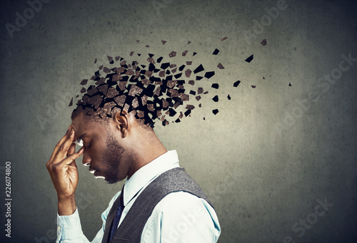 Photo Side profile of a sad man losing parts of head as symbol of decreased mind function