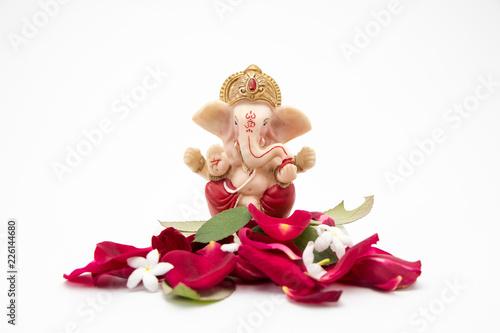 Canvas Print Lord Ganesha Idol with rose petals on white background, ganesh chaurthi, ganesh