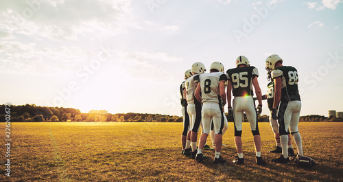 Fototapeta American football players talking strategy together during pract
