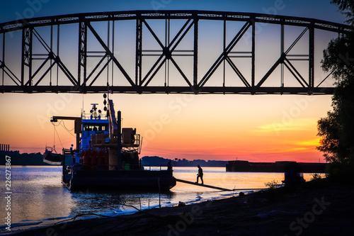 Fotografija Sunset with bridge, barge, and silhouette of dockworker