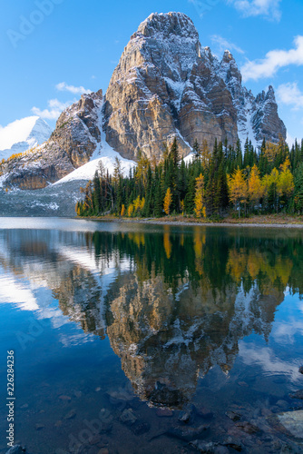 Photo Sunburst Peak reflects perfectly into Sunburst Lake full of fall colors