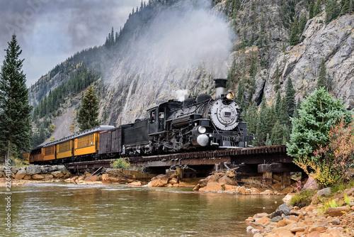 Obraz na płótnie Steam Train Crossing a Trestle Bridge in the Mountains