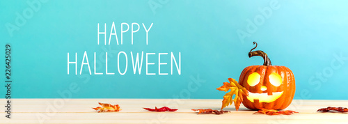Happy Halloween message with pumpkin with leaves on a blue background