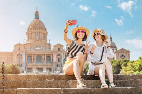 Fototapeta premium Dwie młode szczęśliwe przyjaciółki turystów przytulające się na tle Narodowego Muzeum Sztuki w pobliżu Plaza of Spain i Fontanny Montjuic w Barcelonie
