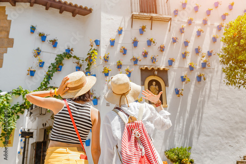 Murais de parede Two girls tourist admiring great view of flowerpots on the white walls on famous