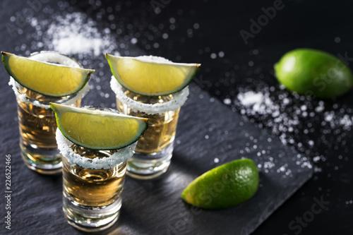 Golden tequila on black background