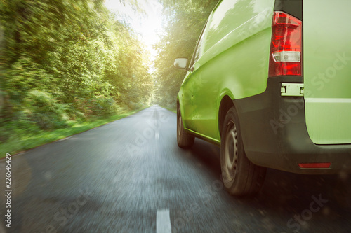 Grüner Transporter fährt durch den Wald