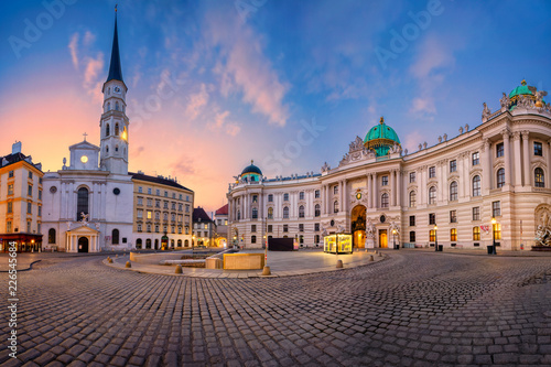 Fototapeta premium Wiedeń, Austria. Pejzaż miejski Wiednia z kościołem św. Michała i znajdujący się na placu św. Michała podczas wschodu słońca.