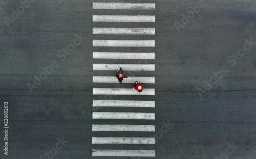 Aerial. Two pedestrians walk on a pedestrian crossing. Fototapet