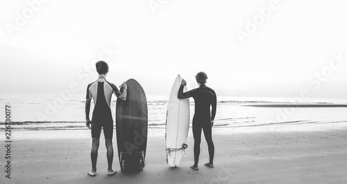 Young surfers waiting the waves on the beach - Sport friends getting ready for surfing - Extreme sport, youth lifestyle and recreation concept - Black and white editing