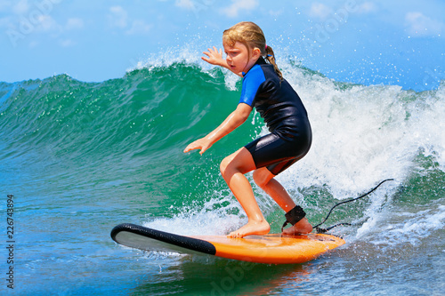 Fotografia Happy baby girl - young surfer ride on surfboard with fun on sea waves