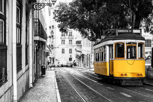 Obraz premium Żółty tramwaj na starych ulicach Lizbony, Portugalia, popularna atrakcja turystyczna i miejsce docelowe. Czarno-biały obraz z kolorowym tramwajem.