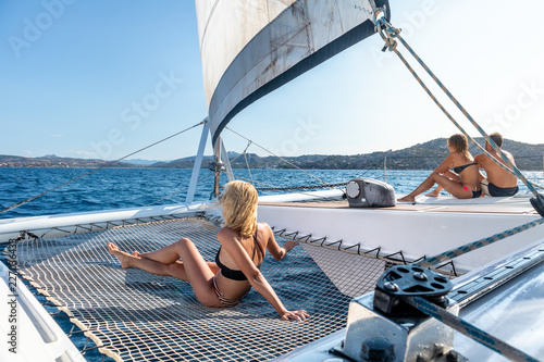 Canvas People tanning and relaxing on a summer sailin cruise, sitting on a luxury catamaran near picture perfect Palau town, Sardinia, Italy