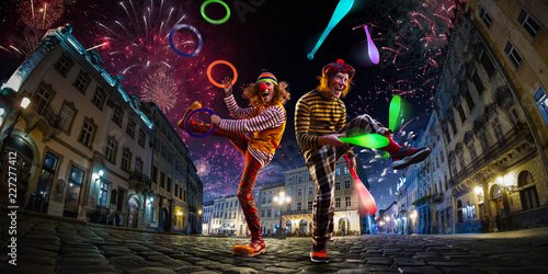 Fotografia Night street circus performance whit two clowns, juggler