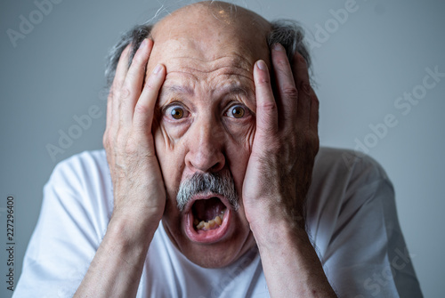 Stampa su Tela Close up of scared and shocked senior man gesturing in fear with hands and face