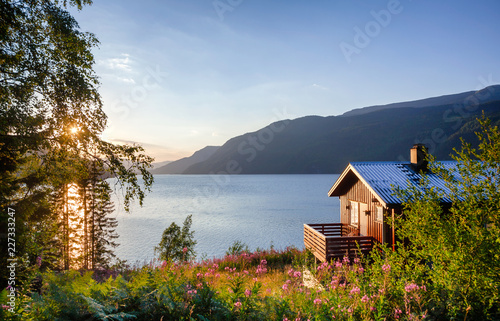 Wooden summerhouse with terrace overlooking scenic lake at sunset in Norway Scan Fototapeta