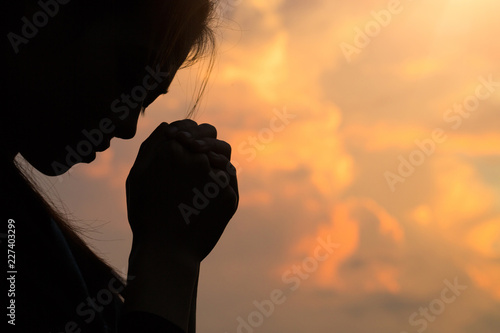 Stampa su Tela Silhouette of woman hands praying to god with the bible