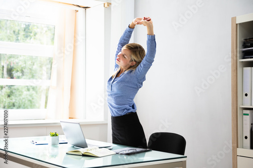 Businesswoman Stretching Her Arms At Workplace Fototapeta