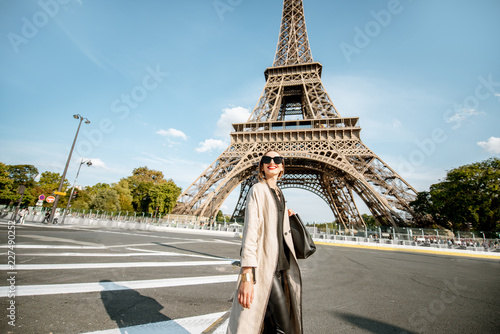 Fototapeta Lifestyle portrait of a young stylish woman crossing the street in front of the