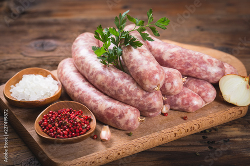 Raw sausages on the wooden board Fototapeta