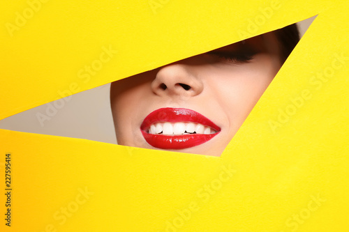 Stampa su Tela View of beautiful young woman with red lips through cutout in color paper, close