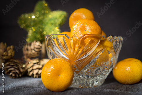 Crystal vase with a tangerine on grey background.