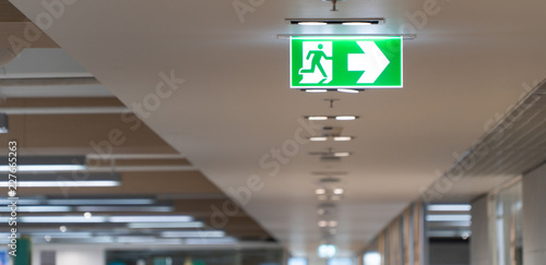 Fotografija Green fire escape sign hang on the ceiling in the office.