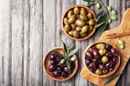 Pickled olives served in bowls from olive wood on rustic kitchen table top view.