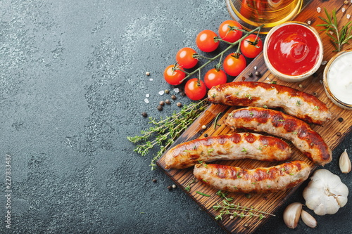 Fried sausages with sauces and herbs on a wooden serving Board Fototapeta