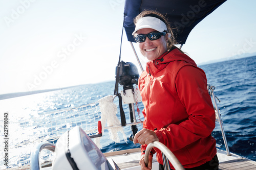 Obraz na plátně Attractive strong woman sailing with her boat