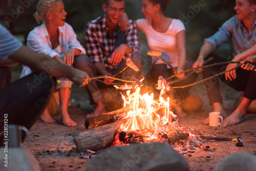 Tablou Canvas young friends relaxing around campfire