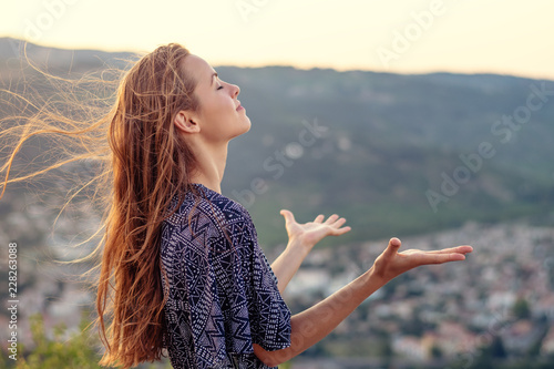 Christian worship and praise. A young woman with her hands raised in worship and praise to god.