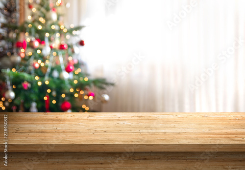 empty wood table top and blur of room with a christmas tree background, suitable for montage product display