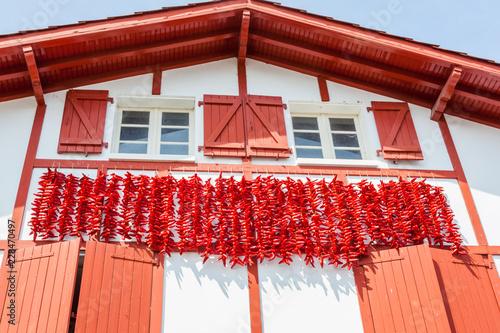 Cordes de piments d'Espelette séchant sur les façades des maisons en pays Basque Fototapeta