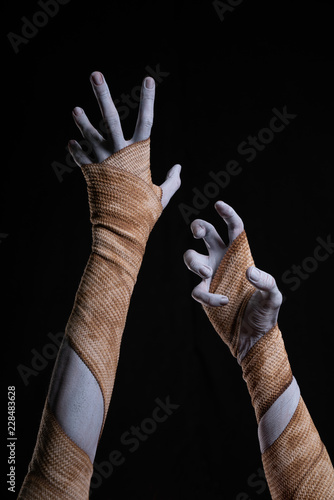 Leinwand Poster Spooky mummy stretching up hands wrapped in bandages