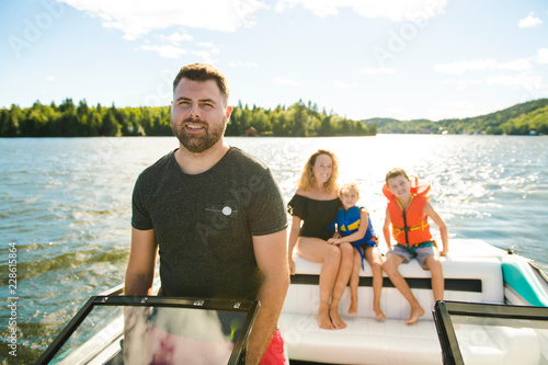 Fotografering Man driving boat on holiday with his son kids and his wife