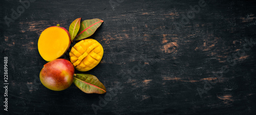 Photo Mango with leaves on a black wooden background