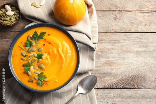 Flat lay composition with pumpkin cream soup in bowl on wooden background. Space for text