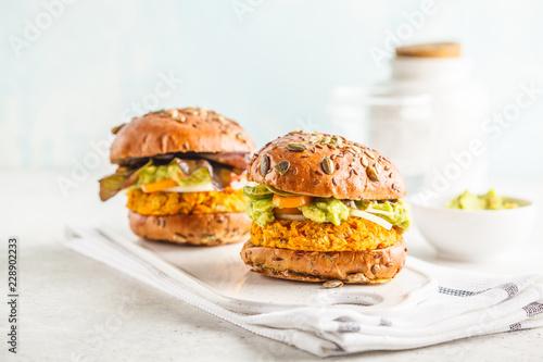 Vegan sweet potato (or pumpkin) burgers on white background. Vegetable burgers, avocado, vegetables and buns.