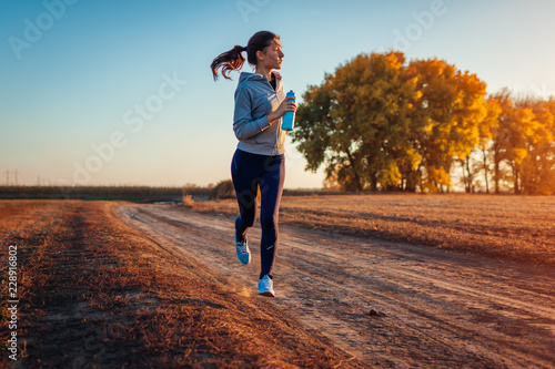 Woman running in autumn field at sunset. Healthy lifestyle concept. Active sportive people