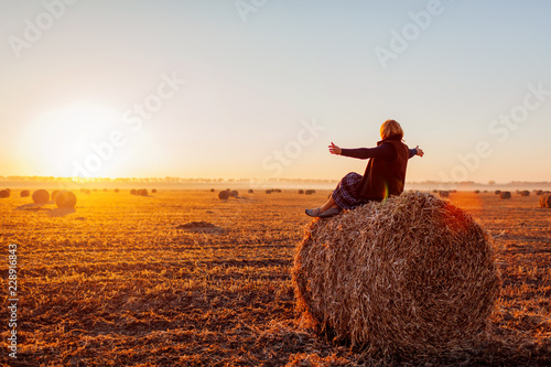 Canvastavla Happy middle-aged woman sitting on haystack in autumn field and feeling free wit