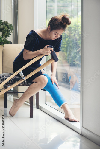 Wallpaper Mural injury woman with leg splint sitting and wooden crutches at hospital
