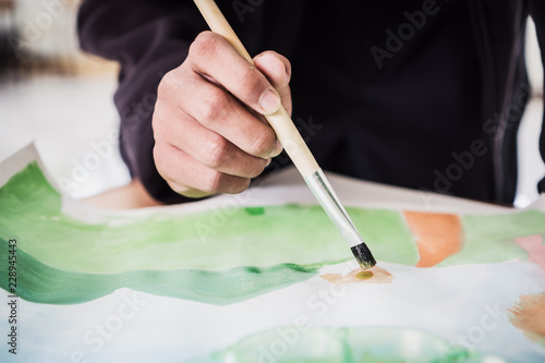 Foto Artist painting watercolor abstract of landscape with brush drawing on paper for creation at studio for relax and hobby