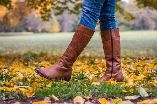 Woman wearing brown leather boot and walking in fallen leaves. Fashion model in autumn park
