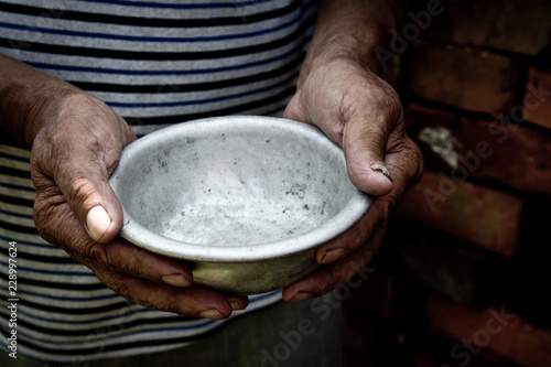 Fototapeta The poor old man's hands hold an empty bowl