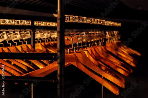 Fotografia Wooden hangers with numbers in dark cloakroom